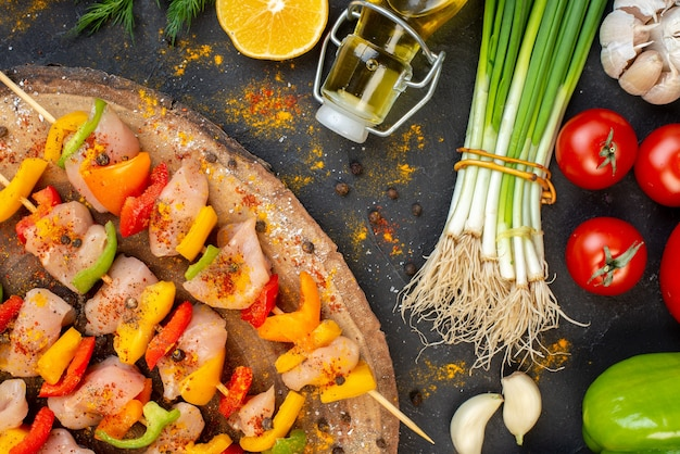 Spiedini di pollo crudo a metà vista dall'alto su tavola di legno naturale e verdure fresche al buio