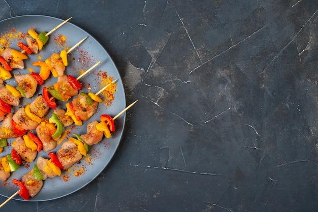 Spiedini di pollo crudo a metà vista dall'alto con spezie su tavola di legno su oscurità