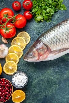 Mezza vista dall'alto pesce crudo pomodori fette di limone prezzemolo sul tavolo della cucina