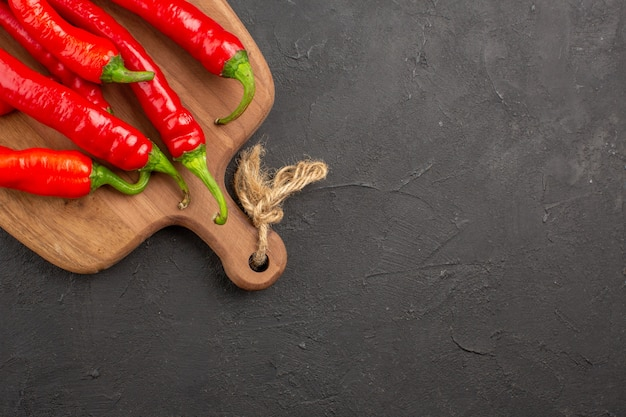Top half view red hot peppers on a chopping board on the black table