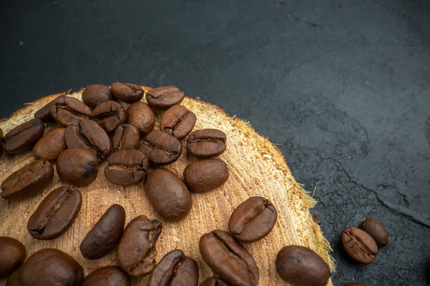 Top half view roasted coffee seeds on wood board on dark background