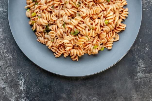 어두운 테이블에 둥근 접시에 상단 절반보기 rotini 파스타