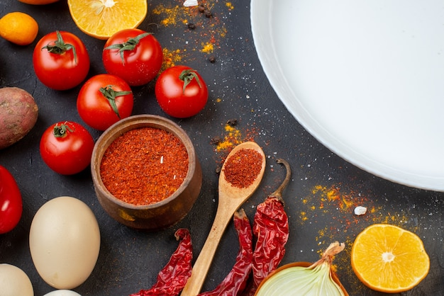 Mezza vista superiore piatto rotondo aglio peperoncino in polvere in una piccola ciotola pomodori uova sul tavolo