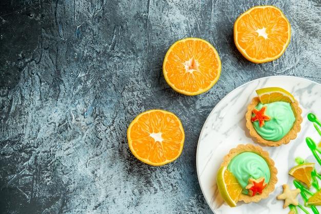 타원형 접시에 녹색 과자 크림과 레몬 슬라이스가있는 상단 절반보기 작은 타르트는 어두운 표면 여유 공간에 오렌지를 자릅니다.