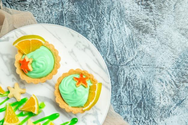 베이지 색 목도리에 접시에 녹색 과자 크림과 레몬 슬라이스가있는 상단 절반보기 작은 타르트는 여유 공간이있는 어두운 표면에 오렌지를 잘라냅니다.