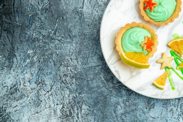 어두운 표면 여유 공간에 접시에 녹색 과자 크림과 레몬 슬라이스가있는 상단 절반보기 작은 타르트