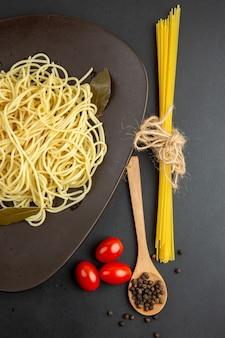 Spaghetti a metà vista dall'alto con foglie di alloro su forchetta cucchiaio di legno pomodorini su superficie nera