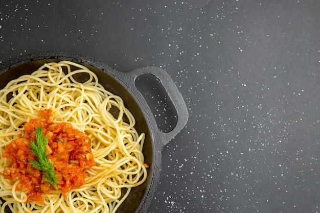 黒いテーブルの空きスペースにフライパンでソースと上半分のビュースパゲッティ