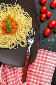 Spaghetti a metà vista dall'alto con salsa su forchetta pomodorini su tavola nera