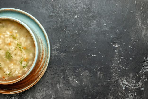 Zuppa di stelle a metà vista dall'alto in una ciotola su sfondo scuro