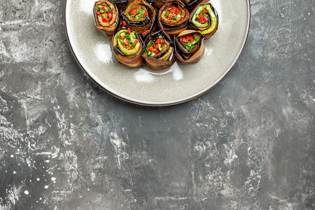 Top half view stuffed aubergine rolls on grey background with free space