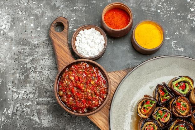 회색 흰색 배경에 작은 볼에 다양한 향신료를 처리한 나무 서빙 보드의 그릇에 있는 타원형 접시 아지카의 상단 절반 보기 박제 aubergine 롤