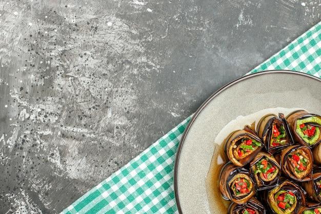 灰色の背景に白い楕円形のプレートターコイズホワイトのテーブルクロスで上半分のビュー詰め茄子ロール