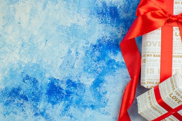 파란색 배경 복사 장소에 빨간 리본이 달린 상위 절반 보기 발렌타인 데이 선물