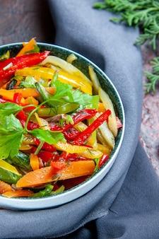 Insalata di verdure vista metà superiore in scialle blu oltremare della ciotola sul tavolo rosso scuro