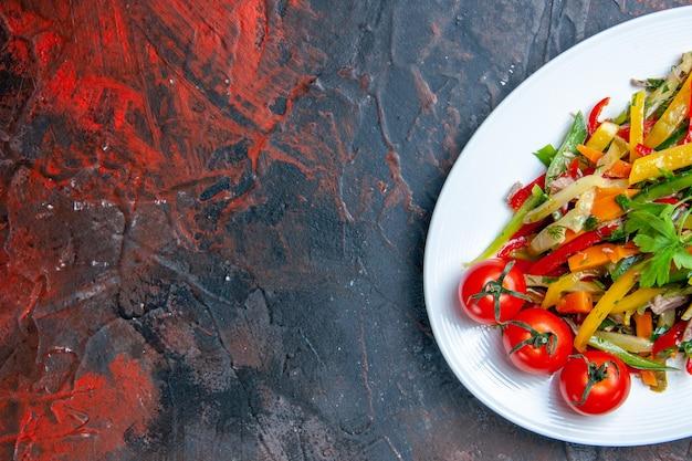 濃い赤の表面の空きスペースに楕円形のプレートの上半分ビュー野菜サラダ