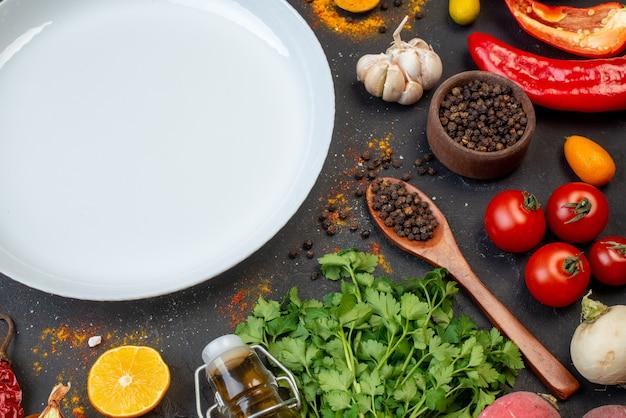 Vista dall'alto piatto rotondo bianco pepe nero in una piccola ciotola bottiglia aglio coriandolo sul tavolo