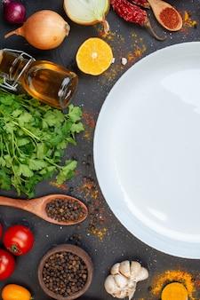 Mezza vista superiore piatto rotondo bianco pepe nero in una piccola ciotola pomodori all'aglio
