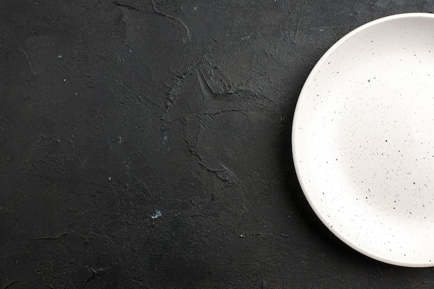 Top half view white salad plate on dark table free space