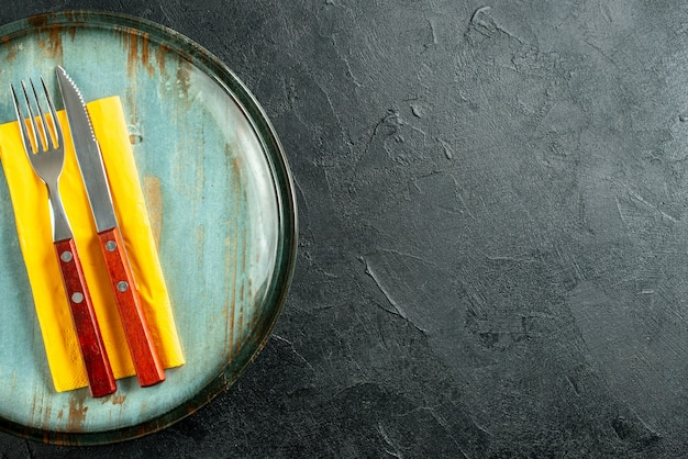 Верхняя половина вида желтая салфетка, нож и вилка на тарелках на черном столе с копией пространства