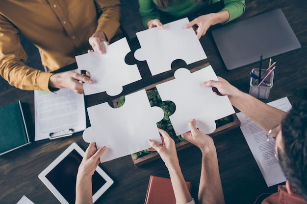 Top above high angle view  of focused freelancer people sit table desk merge paper puzzle pieces elements trust support company
