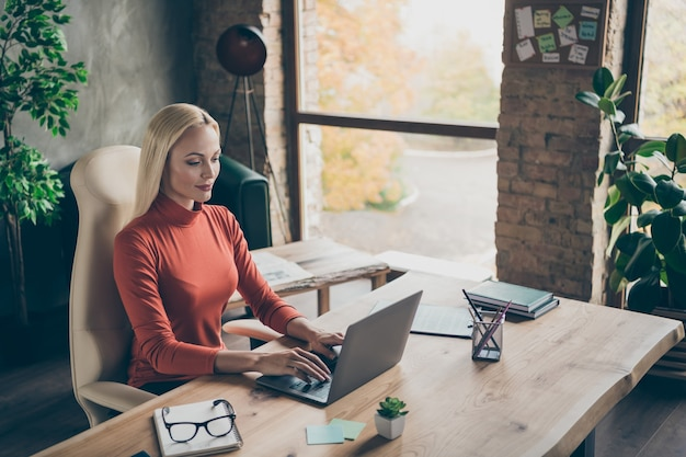 Top above high angle view photo of cheerful positive pretty entrepreneur looking into laptop screen with glasses lying nearby in light of window