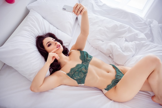 Top above high angle view portrait of her she nice fit slim sporty slender perfect shaped attractive lovable girl lying on bed taking selfie sending photos husband light white interior house apartment