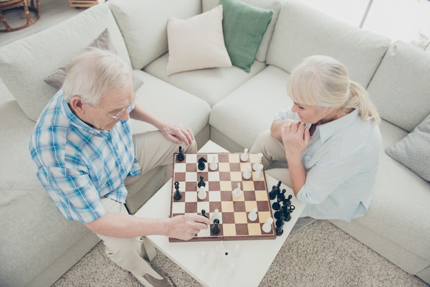 Top above high angle view of two nice focused people creating new move amateur championship in light white interior living-room house