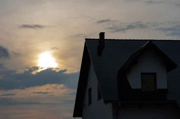 Top of the house with a roof and a loft at sunset.