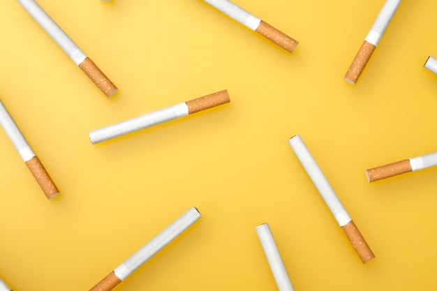 A top  image of several cigarettes. flat lay. cigarettes on yellow.