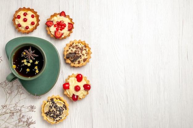 左上の白い木製のテーブルにお茶とさまざまなクッキーを表示 無料写真