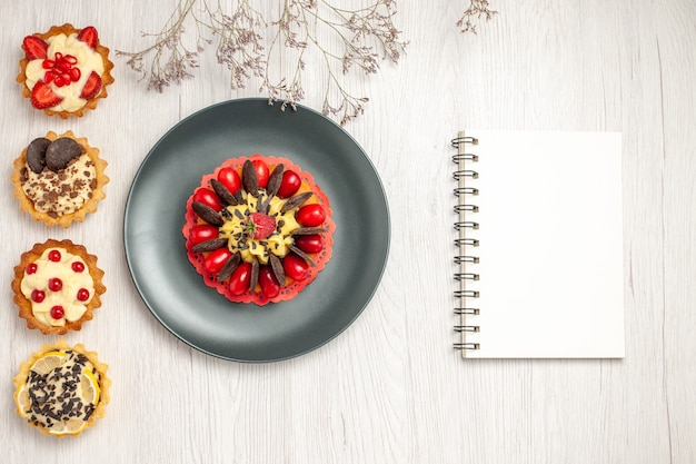 Top left side view berry cake in a grey plate and from top to the bottom different tarts and a notebookon the white wooden ground