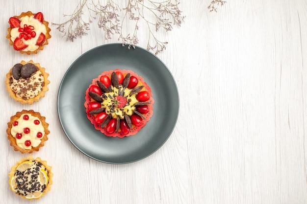 Torta di frutti di bosco in alto a sinistra vista in un piatto grigio e dall'alto verso il basso diverse torte sul fondo di legno bianco