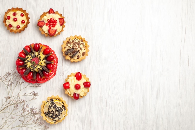 Top left side view berry cake surrounded berry and chocolate tarts on the white wooden ground