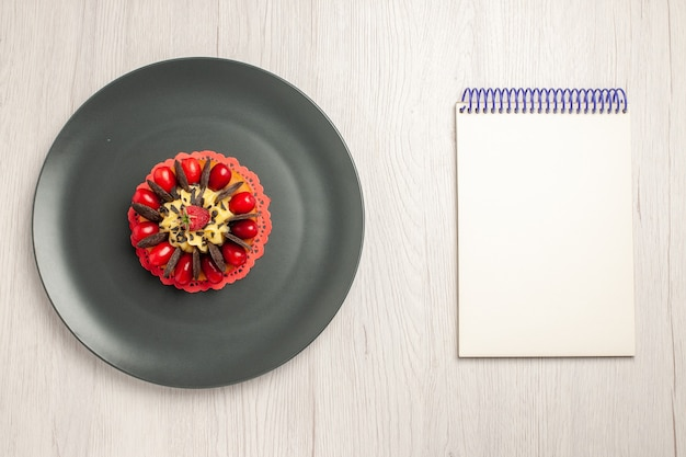Top left side view chocolate cake rounded with cornel and raspberry in the center in the grey plate and a notebook on the white wooden background