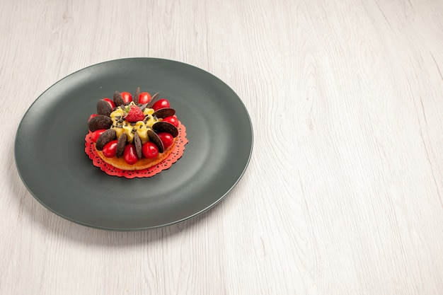 Top left side view chocolate cake rounded with cornel and raspberry in the center in the grey plate on the white wooden table