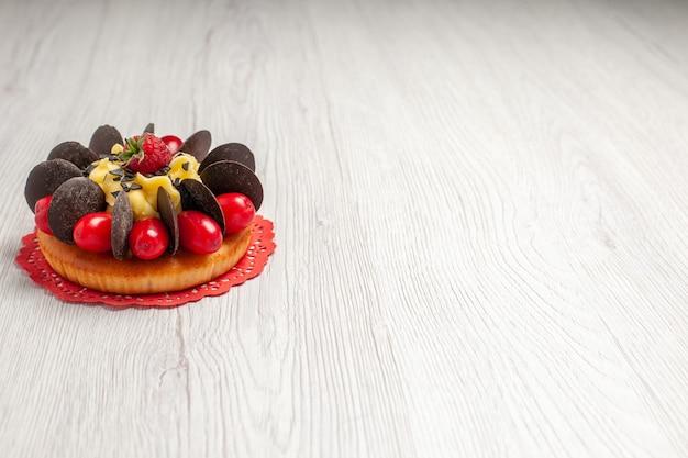 Torta al cioccolato vista lato sinistro superiore con frutti di bosco sul centrino di pizzo ovale rosso sul tavolo di legno bianco