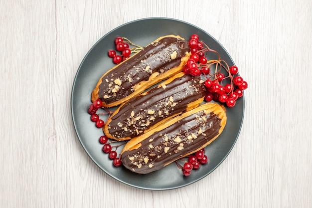 In alto a sinistra vista laterale eclairs al cioccolato e ribes sul piatto grigio sul ritmo di terra in legno bianco