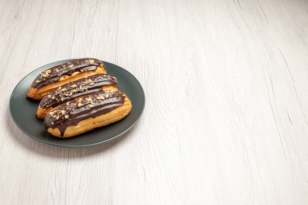 Top left side view chocolate eclairs on the grey plate on the white wooden ground