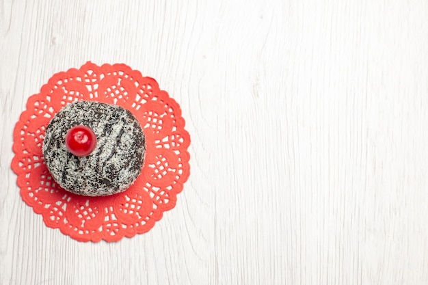 左上のビュー白い木製のテーブルの上の赤い楕円形のレースのドイリーにサワーチェリーとココアケーキ