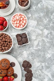Vista laterale in alto a sinistra biscotti fragole e cioccolatini rotondi sul piatto ovale ciotole con caramelle fragole e cioccolatini cereali e una tazza di tè sul tavolo grigio-bianco