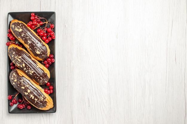 Вверху слева вид шоколадных эклеров и смородины на черной прямоугольной тарелке на белой деревянной основе