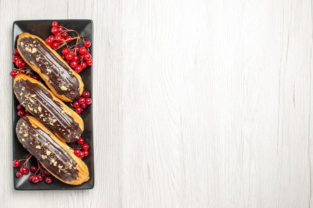 Top left view chocolate eclairs and currants on the black rectangular plate on the white wooden ground