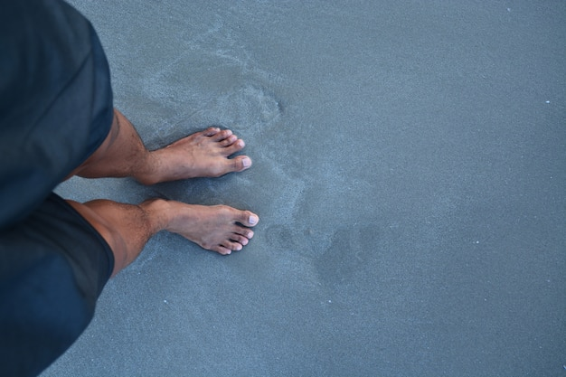 The top of man feet with no shoe on the sand