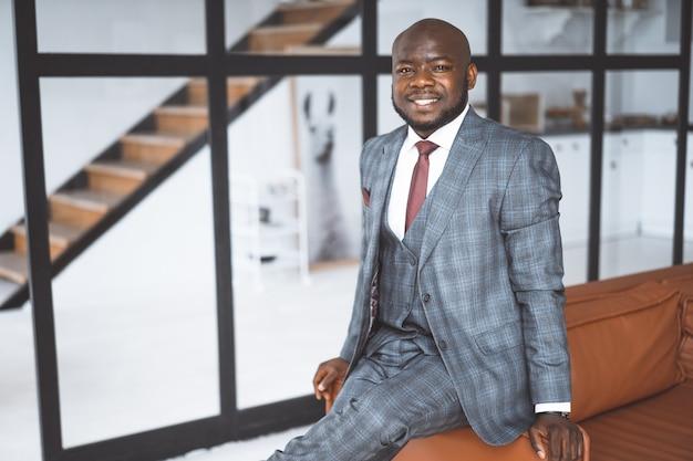 ホテルのトップマネージャーがゲストを歓迎しますホテルビジネスアフロアメリカンマン笑顔マナのコンセプト...