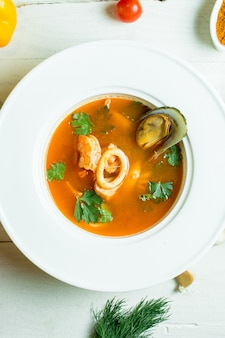 Top  mussel soup with tomato and herbs in white bowl