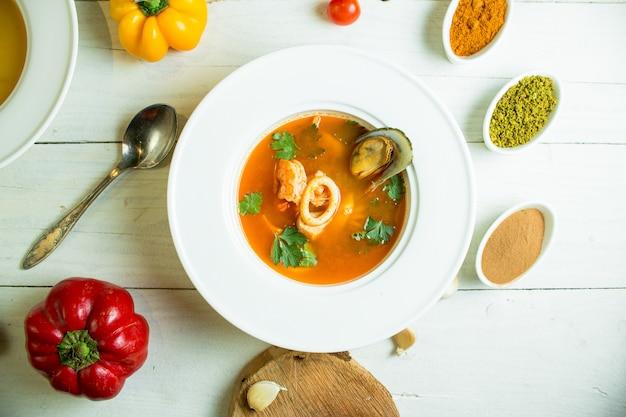 Zuppa di cozze con pomodoro ed erbe in una ciotola bianca
