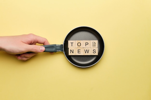 Top news concept on a frying pan on a yellow background.