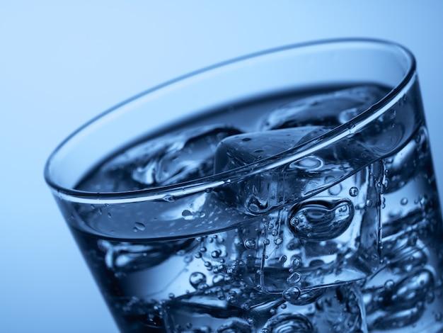 밝은 파란색 배경에 얼음 조각이 있는 물 한 잔
