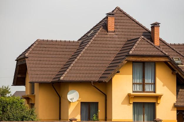 Вершина большого современного дорогого жилого дома с черепичной коричневой крышей, высокими кирпичными трубами, лепными стенами и пластиковыми мансардными окнами на голубом небе